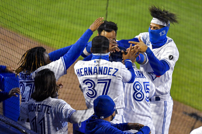 Toronto Blue Jays' Alejandro Kirk (85) is mobbed by teammates Vladimir Guerrero Jr., left, Teoscar Hernández (37) and Lourdes Gurriel Jr., right, after hitting a solo home run against the New York Yankees during the seventh inning of a baseball game in Buffalo, N.Y., Monday, Sept. 21, 2020. (AP Photo/Adrian Kraus)