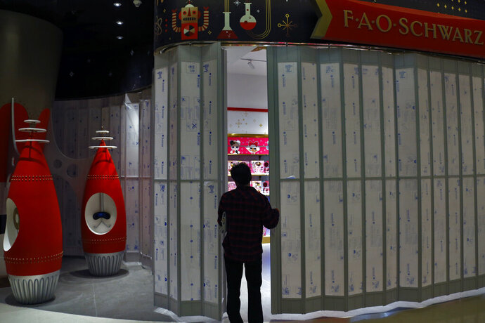 A worker opens a door as he and other workers prepare to set up the new upcoming FAO Schwarz toy store at the capital city's popular shopping mall in Beijing, Thursday, May 23, 2019. An escalating trade war between the U.S. and China could mean higher prices on a broad array of products from toys to clothing. But some retailers will be less equipped to handle the pain than others, leaving consumers to carry the load. (AP Photo/Andy Wong)