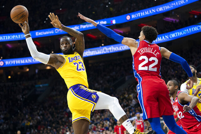 Los Angeles Lakers' LeBron James, left, passes the ball with Philadelphia 76ers' Matisse Thybulle, right, defending during the first half of an NBA basketball game, Saturday, Jan. 25, 2020, in Philadelphia. (AP Photo/Chris Szagola)