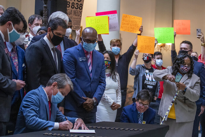 Gov. Brian Kemp, lower left, signs HB 426, hate-crimes legislation, into law as demonstrators hold signs asking him to veto HB 838 in the North Wing of the Georgia State Capitol building Friday, June 26, 2020. Kemp signed into law House Bill 426 which would impose additional penalties for crimes motivated by the victim's race, color, religion, national origin, sexual orientation, gender or disability. (Alyssa Pointer/Atlanta Journal-Constitution via AP)