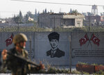 Shortly after the Turkish operation inside Syria had started and backdropped by a graffiti of modern Turkey's founder Mustafa Kemal Ataturk, a Turkish soldier stands on the Turkish side of the border in Akcakale, Sanliurfa province, southeastern Turkey, Wednesday, Oct. 9, 2019. Turkey launched a military operation Wednesday against Kurdish fighters in northeastern Syria after U.S. forces pulled back from the area, with a series of airstrikes hitting a town on Syria's northern border. (AP Photo/Lefteris Pitarakis)