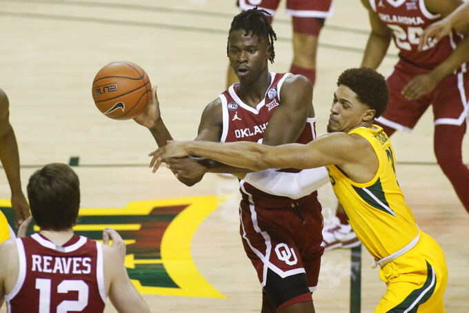 Oklahoma forward Victor Iwuakor, left, passes the ball as he is defended by Baylor guard MaCio Teague, right, during the first half of an NCAA college basketball game on Wednesday, Jan. 6, 2021, in Waco, Texas. (AP Photo/Ray Carlin)