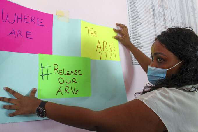 A protester holds a placard during a demonstration over shortages of anti-retroviral (ARV) medicines, organized by people living with HIV or AIDS, sex-workers, members of the LGBT community, and their supporters, in the port city of Mombasa, Kenya Thursday, April 22, 2021. Kenyans living with HIV say their lives are in danger due to a shortage of anti-retroviral drugs donated by the United States amid a dispute between the U.S. aid agency and the Kenyan government. (AP Photo)