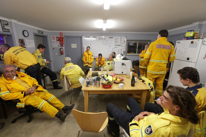 In this Jan. 10, 2020, photo, firefighters and army personnel gather in a common room at the Rural Fire Service fire house at Burragate, Australia. It seemed imminent to those hunkering at the fire station that