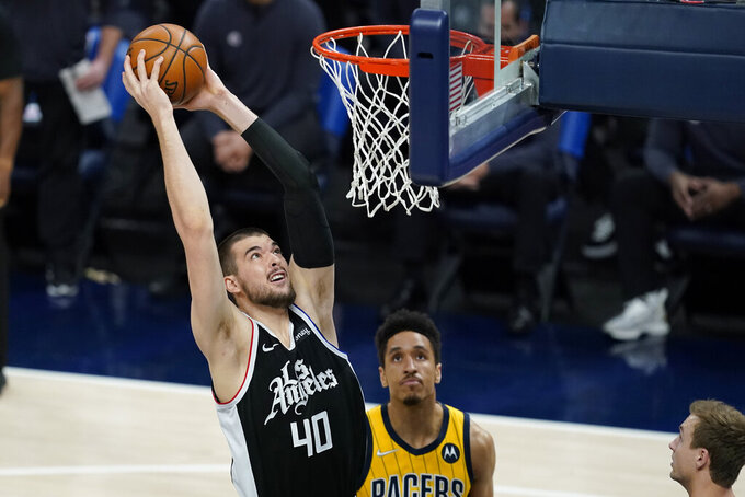 Los Angeles Clippers' Ivica Zubac (40) goes up for a dunk against Indiana Pacers' Malcolm Brogdon (7) during the first half of an NBA basketball game, Tuesday, April 13, 2021, in Indianapolis. (AP Photo/Darron Cummings)