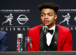 File-This Dec. 14, 2019, NCAA college football player and Heisman Trophy finalist, Ohio State quarterback Justin Fields talks to the media during a news conference before the start of the Heisman Trophy ceremony, Saturday, Dec. 14, 2019, in New York. Fields, a sophomore and the Buckeyes' Heisman Trophy finalist quarterback, said online classes allow him to split his time between studying at home or relaxing with Netflix and the Woody Hayes Athletic Center, where besides football facilities there is a new lavish lounge for players that offers made-to-order meals, massage chairs, video games on big screens and a cryogenic chamber. (AP Photo/Jason Szenes, File)