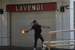 A protester throws a Molotov cocktail at a police station in Hong Kong, Sunday, Oct. 20, 2019. Hong Kong protesters again flooded streets on Sunday, ignoring a police ban on the rally and demanding the government meet their demands for accountability and political rights. (AP Photo/Kin Cheung)