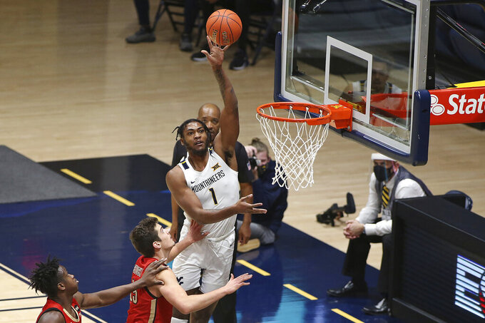 West Virginia forward Derek Culver (1) shoots while defended by Northeastern forward Coleman Stucke (15) during the second half of an NCAA college basketball game Tuesday, Dec. 29, 2020, in Morgantown, W.Va. (AP Photo/Kathleen Batten)