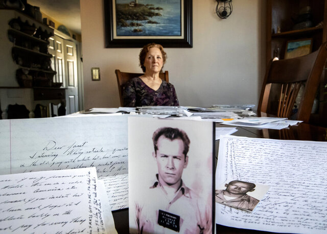 Janet Uhlar sits for a photo at her dining room table with an arrangement of letters and pictures she received through her correspondence with imprisoned Boston organized crime boss James