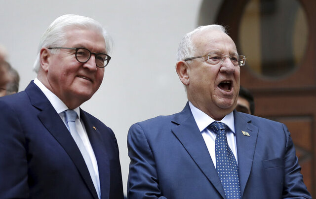 German President Frank-Walter Steinmeier, left, and Israel's President Reuven Rivlin, right, sing as they attend a performance of the school choir during their visit at the Jewish Moses Mendelssohn school in Berlin, Germany, Tuesday, Jan. 28, 2020. (AP Photo/Michael Sohn, pool)