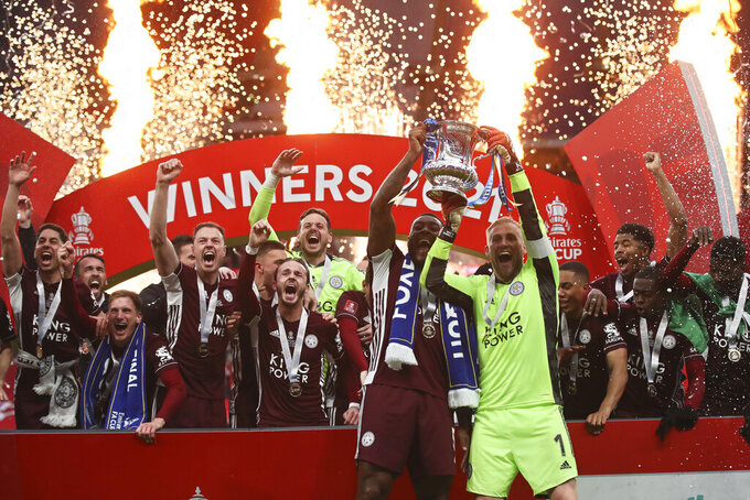 Leicester's goalkeeper Kasper Schmeichel, right, and Leicester's Wes Morgan lift the trophy after winning the FA Cup final soccer match between Chelsea and Leicester City at Wembley Stadium in London, England, Saturday, May 15, 2021. Leicester won 1-0. (Nick Potts/Pool via AP)