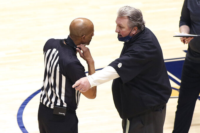 West Virginia coach Bob Huggins speaks with an official during the second half of an NCAA college basketball game against North Texas Friday, Dec. 11, 2020, in Morgantown, W.Va. (AP Photo/Kathleen Batten)