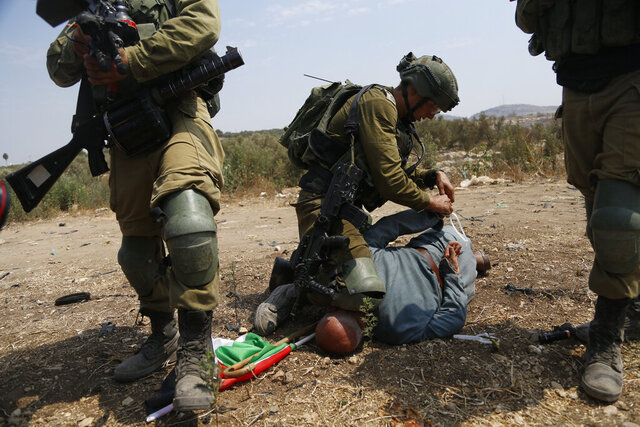 Israeli soldiers detain a Palestinian during a protest against expansion of Israeli settlements in the village of Shufa in the West Bank, Tuesday, Sep. 1, 2020.(AP Photo/Majdi Mohammed)