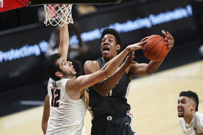 Oregon State's Roman Silva (12) blocks a shot by Washington State's Dishon Jackson (21) during the first half of an NCAA college basketball game in Corvallis, Ore., Saturday, Feb. 6, 2021. (AP Photo/Amanda Loman)