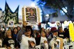 Demonstrators hold posters of the four victims of Monday's police shooting, during a march against police brutality, in Buenos Aires, Argentina, Friday, May. 24, 2019. Argentines protested after officers on Monday fired shots that led to the deaths of three teenagers and a young man in a car chase. (AP Photo/Tomas F. Cuesta)