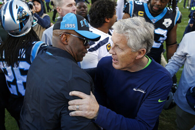 Carolina Panthers interim head coach Perry Fewell, left, and Seattle Seahawks head coach Pete Carroll hug foillowing an NFL football game in Charlotte, N.C., Sunday, Dec. 15, 2019. (AP Photo/Brian Blanco)