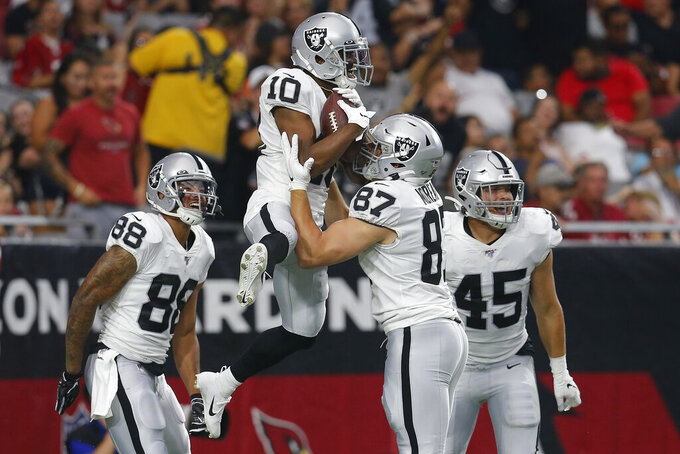 Oakland Raiders wide receiver Rico Gafford (10) celebrates his touchdown against the Arizona Cardinals with teammate tight end Foster Moreau (87) during the first half of an an NFL football game, Thursday, Aug. 15, 2019, in Glendale, Ariz. (AP Photo/Ralph Freso)