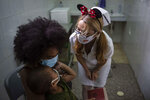 A nurse consoles a child after he was injected with a dose with a dose of the Soberana-02 COVID-19 vaccine, at a clinic in Havana, Cuba, Thursday, Sept. 16, 2021. Cuba began inoculating children as young as 2-years-old with locally developed vaccines on Thursday. (AP Photo/Ramon Espinosa)