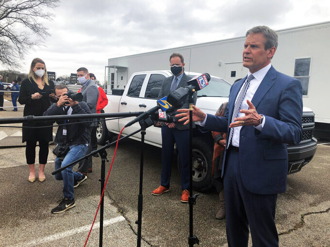 Tennessee Gov. Bill Lee, right, speaks with reporters about vaccine distribution problems in the state's most populous county on Friday, Feb. 26, 2021, in Memphis, Tenn. (AP Photo/Adrian Sainz)