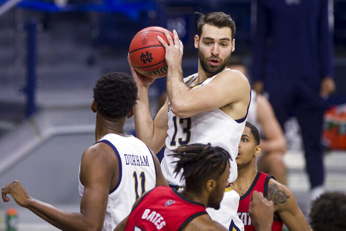 Notre Dame's Nikola Djogo (13) grabs a rebound during the first half of an NCAA college basketball game against North Carolina State on Wednesday, March 3, 2021, in South Bend, Ind. North Carolina State won 80-69. (AP Photo/Robert Franklin)