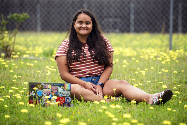 In this May 21, 2020, photo, Ileana Valdez, 20, an undergrad student at Yale, poses for a photo outside of her home in Red Oak, Texas. Valdez created an online dating site for college students called OKZoomer.