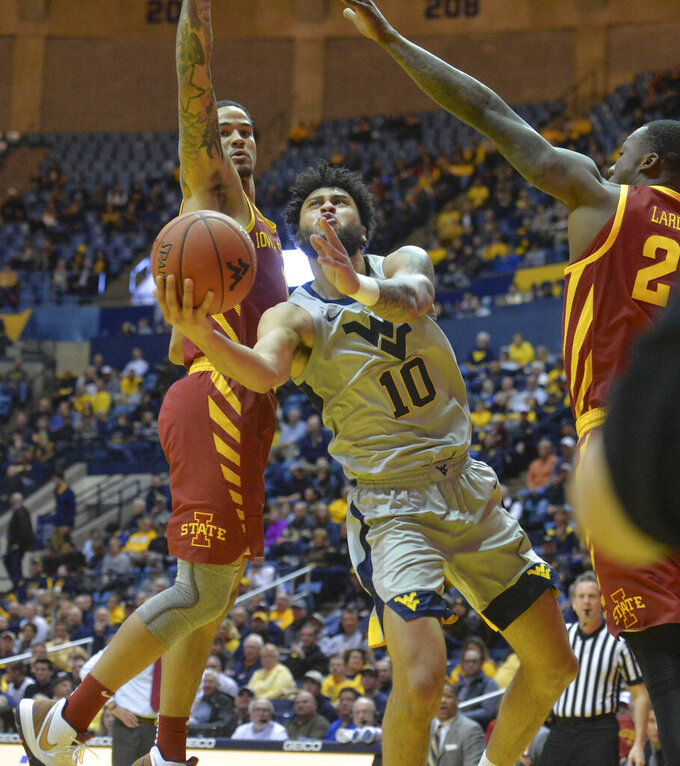 West Virginia guard Jermaine Haley (10) shoots while being defended by Iowa State guard Nick Weiler-Babb, left, during the first half of an NCAA college basketball game Wednesday, March 6, 2019, in Morgantown, W.Va. (William Wotring/The Dominion-Post via AP)