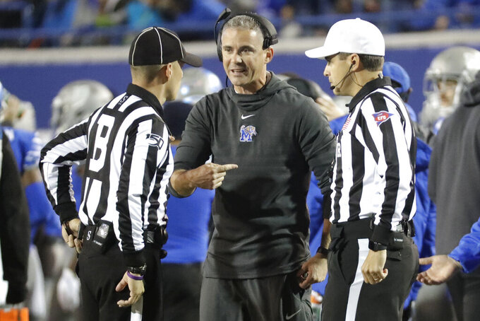 Memphis head coach Mike Norvell talks with back judge Chris Bikowski, left, and referee Adam Savoie, right, in the first half of an NCAA college football game between Memphis and SMU Saturday, Nov. 2, 2019, in Memphis, Tenn. (AP Photo/Mark Humphrey)