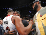 LeBron James, right, watches as Miami Heat guard Dwyane Wade (3) embraces Chris Paul at the Heat's NBA basketball game against the New York Knicks, Wednesday, April 10, 2019, in New York. (AP Photo/Kathy Willens)