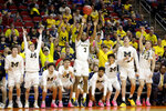 The Michigan bench joins in with Zavier Simpson (3) as he shoots for three points during the second half of a first round men's college basketball game against Montana in the NCAA Tournament in Des Moines, Iowa, Thursday, March 21, 2019. (AP Photo/Nati Harnik)