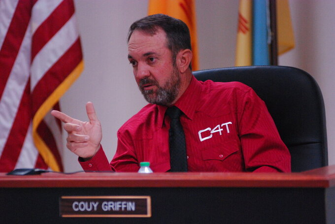 """Otero County Commissioner Couy Griffin presides at a public meeting in Alamogordo, N.M., on Thursday, May 13, 2021, in a shirt with a """"C4T"""" logo that stands for Cowboys for Trump. Griffin founded the support group for President Trump that held horseback parades across the country. Griffin is revered and reviled in politically conservative Otero County as he confronts criminal charges for joining protests on the steps of the U.S. Capitol on Jan. 6. He is fighting for his political future amid a recall initiative and state probes into his finances. (AP Photo/Morgan Lee)"""