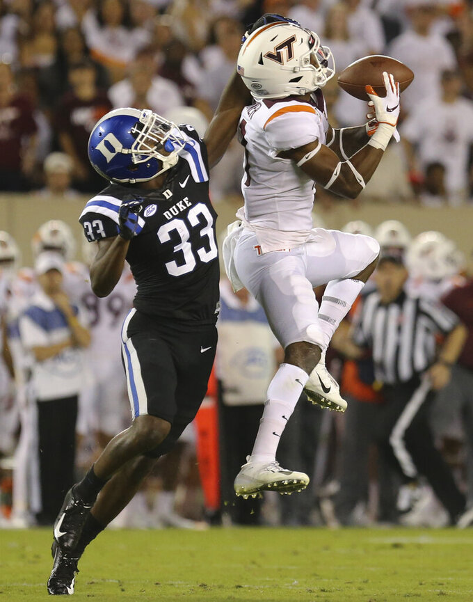 Virginia Tech receiver Tre Turner (11) drops a pass at midfield while defended by Duke's Leonard Johnson (33) in the first half of an NCAA college football game, Friday, Sept. 27, 2019, in Blacksburg, Va. (Matt Gentry/The Roanoke Times via AP)