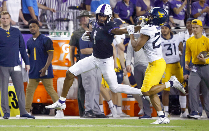 TCU wide receiver Quentin Johnston (1) stiff-arms West Virginia safety Sean Mahone (29) after making a catch for a first down during the first half of an NCAA college football game Saturday, Oct. 23, 2021, in Fort Worth, Texas. (AP Photo/Ron Jenkins)