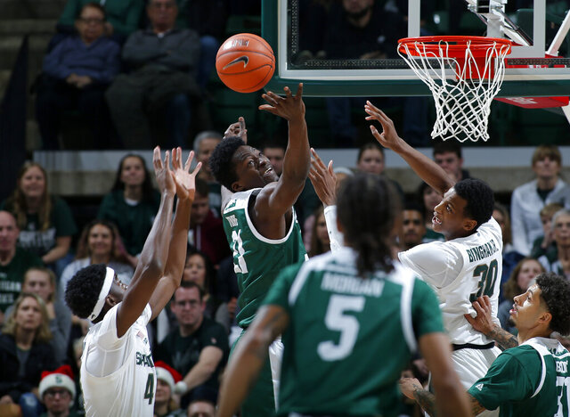 Eastern Michigan's Boubacar Toure, center, and Michigan State's Gabe Brown, left, and Marcus Bingham Jr. (30) vie for a rebound during the first half of an NCAA college basketball game, Saturday, Dec. 21, 2019, in East Lansing, Mich. (AP Photo/Al Goldis)
