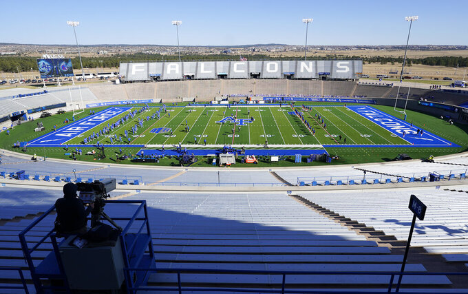 Air Force players, left, warm up with Boise State players in empty Falcon Stadium before an NCAA college football game Saturday Oct. 31, 2020, at Air Force Academy, Colo. (AP Photo/David Zalubowski)