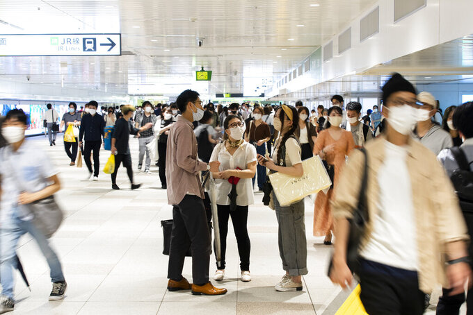 People wearing face masks chat before parting at a train station in Tokyo, Friday, July 9, 2021. A state of emergency began Monday, July 12, 2021, in Tokyo, as the number of new cases is climbing fast and hospital beds are starting to fill just 11 days ahead of the Tokyo Olympics. (AP Photo/Hiro Komae)