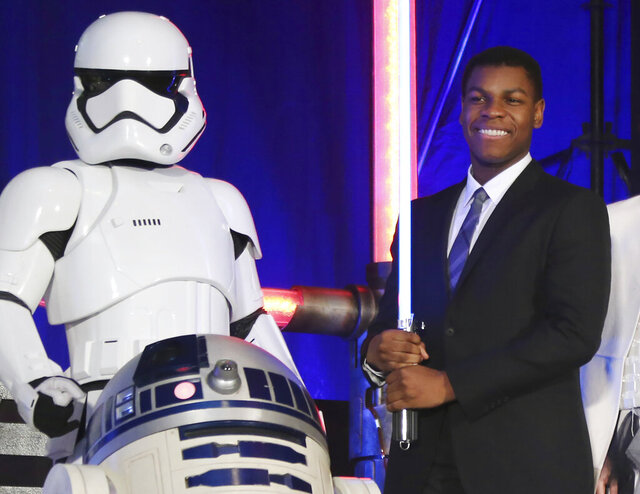 FILE - In this Dec. 10, 2015 file photo, actor John Boyega, right, pose with Star Wars characters during the Japan Premiere of their latest film