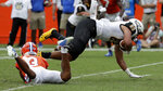 Towson tight end Jason Epps, right, is upended by Florida defensive back Marco Wilson after a pass reception during the first half of an NCAA college football game, Saturday, Sept. 28, 2019, in Gainesville, Fla. (AP Photo/John Raoux)