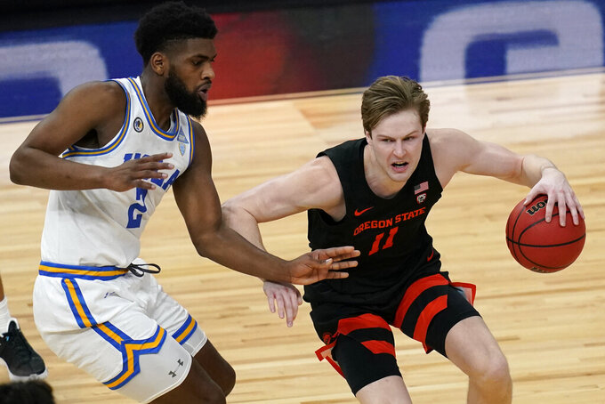 Oregon State's Zach Reichle (11) drives around UCLA's Cody Riley (2) during the first half of an NCAA college basketball game in the quarterfinal round of the Pac-12 men's tournament Thursday, March 11, 2021, in Las Vegas. (AP Photo/John Locher)