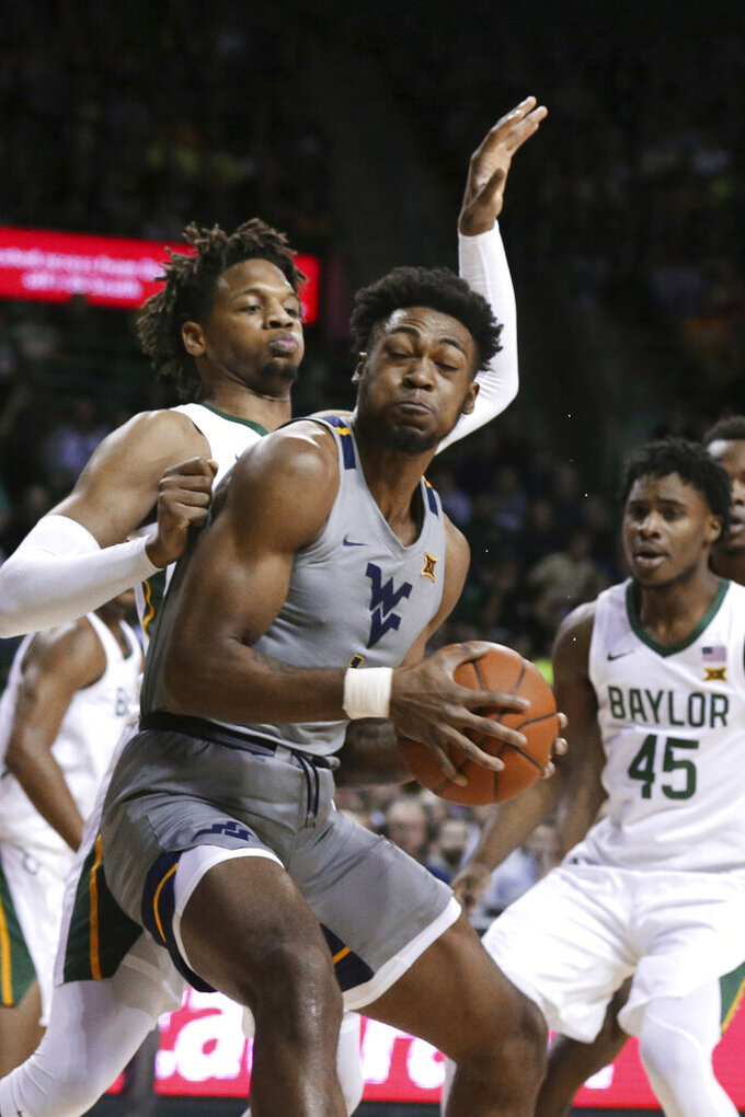 West Virginia forward Derek Culver, right, is guarded by Baylor forward Freddie Gillespie, left, in the first half of an NCAA college basketball game, Saturday, Feb. 15, 2020, in Waco, Texas. (AP Photo/Rod Aydelotte)