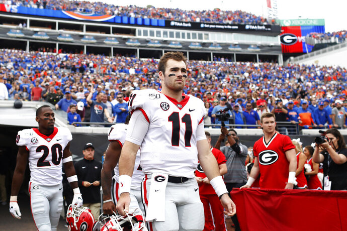 Team captions Georgia quarterback Jake Fromm (11), Georgia running back D'Andre Swift (7), and Georgia defensive back J.R. Reed (20) take the field for the coin flip before the start of an NCAA college football game Saturday, Nov. 2, 2019, in Jacksonville, Fla. Georgia won 24-17.  (Joshua L. Jones/Athens Banner-Herald via AP)