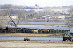 Cows ready for calving stand in a pen on land isolated by the swollen waters of the North Fork of the Elkhorn River, in Norfolk, Neb., Friday, March 15, 2019. Heavy rain falling atop deeply frozen ground has prompted evacuations along swollen rivers in Wisconsin, Nebraska and other Midwestern states. Thousands of people have been urged to evacuate along eastern Nebraska rivers as a massive late-winter storm has pushed streams and rivers out of their banks throughout the Midwest. (AP Photo/Nati Harnik)