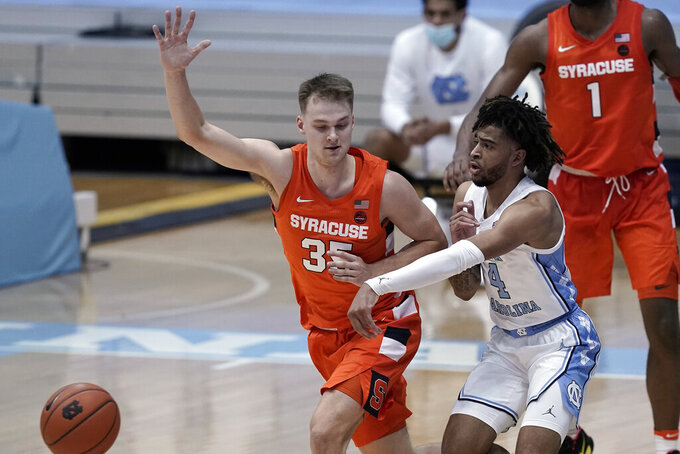 North Carolina guard R.J. Davis (4) passes while Syracuse guard Buddy Boeheim (35) defends during the second half of an NCAA college basketball game in Chapel Hill, N.C., Tuesday, Jan. 12, 2021. (AP Photo/Gerry Broome)