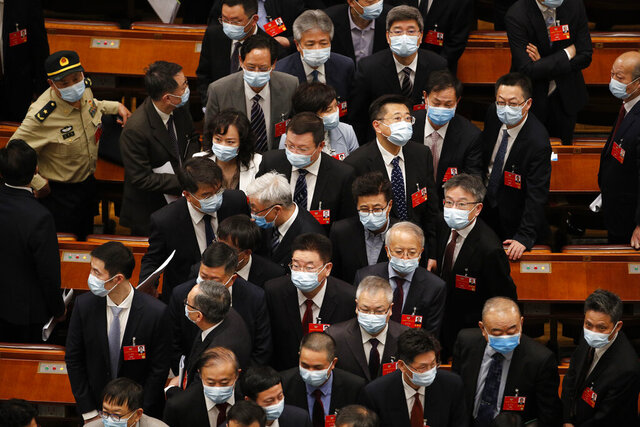 Delegates wearing face masks to protect against the spread of the new coronavirus leave after the opening session of the Chinese People's Political Consultative Conference (CPPCC) at the Great Hall of the People in Beijing, Thursday, May 21, 2020. (AP Photo/Andy Wong, Pool)