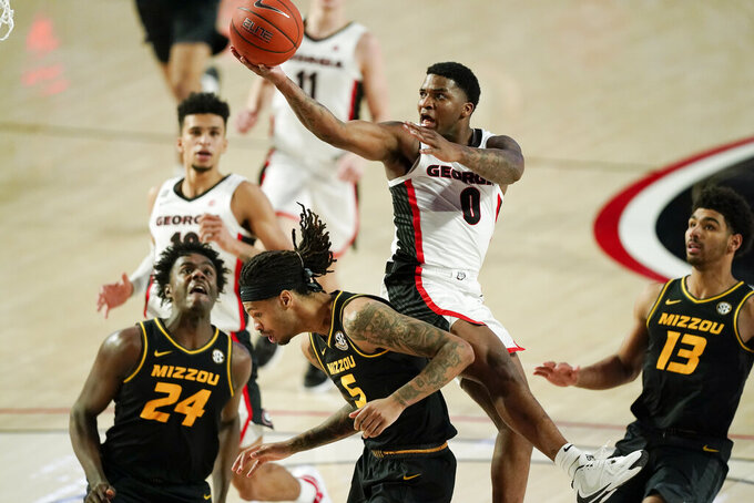 Georgia guard K.D. Johnson (0) is fouled by Missouri forward Mitchell Smith (5) during the second half of an NCAA college basketball game Tuesday, Feb. 16, 2021, in Athens, Ga. (AP Photo/Brynn Anderson)