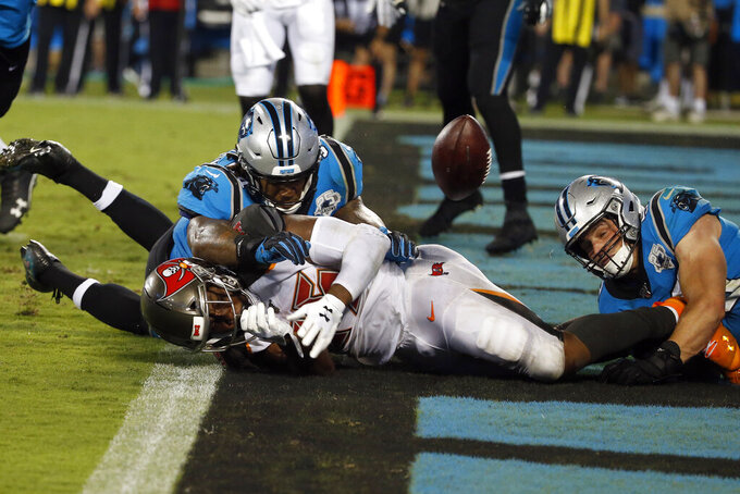 Carolina Panthers outside linebacker Shaq Thompson, left, and middle linebacker Luke Kuechly (59) tackle Tampa Bay Buccaneers running back Peyton Barber for a safety during the second half of an NFL football game in Charlotte, N.C., Thursday, Sept. 12, 2019. (AP Photo/Brian Blanco)