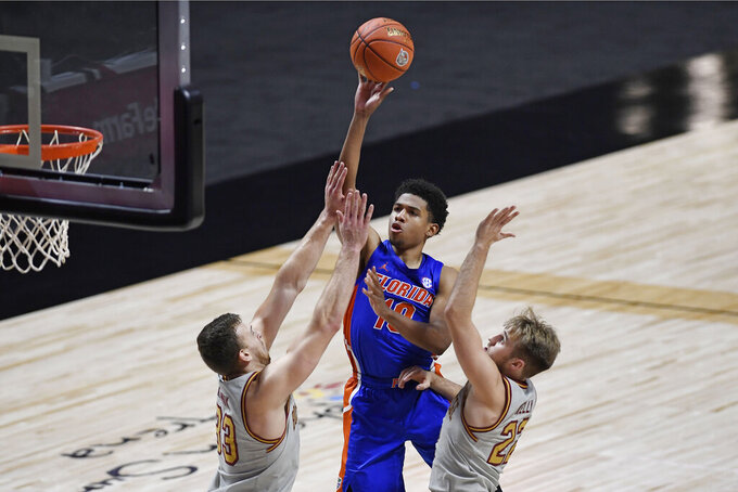 Florida's Noah Locke, center, shoots over Boston College's James Karnik, left, and Rich Kelly during the second half of an NCAA college basketball game Thursday, Dec. 3, 2020, in Uncasville, Conn. (AP Photo/Jessica Hill)