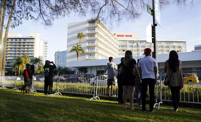 A small group of onlookers look for celebrity arrivals outside the 78th Golden Globe Awards at the Beverly Hilton, Sunday, Feb. 28, 2021, in Beverly Hills, Calif. (AP Photo/Chris Pizzello)