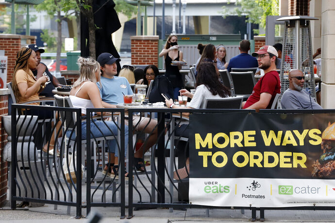 People gather at tables outside Bar Louie in Pittsburgh on Sunday, June 28, 2020. In response to the recent spike in COVID-19 cases in Allegheny County, health officials are ordering all bars and restaurants in the county to stop the sale of alcohol for on-site consumption beginning Tuesday afternoon. (AP Photo/Gene J. Puskar)