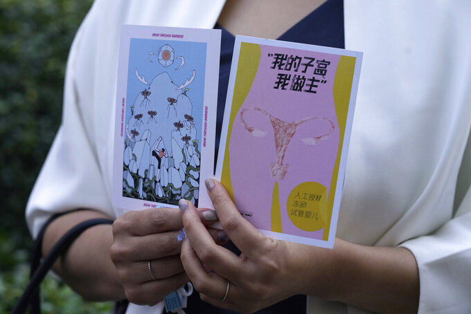 """Teresa Xu holds up cards one of which reads """"My Womb, My Choice"""" before attending a court session at the Chaoyang People's Court in Beijing, China, Friday, Sept. 17, 2021. After almost two years, the unmarried woman suing for the right to freeze her eggs in Beijing, is getting her case heard in court in the first legal challenge of its kind in China. (AP Photo/Ng Han Guan)"""