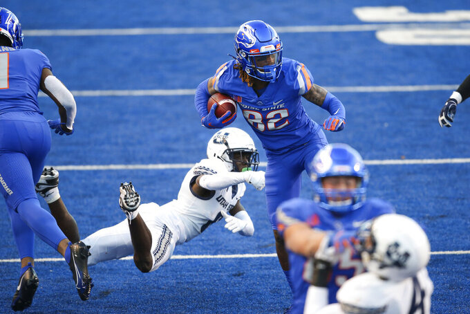 Boise State wide receiver Stefan Cobbs (82) avoids the diving tackle attempt by Utah State cornerback Cam Lampkin (6) in an NCAA college football game Saturday, Oct. 24, 2020, in Boise, Idaho. (AP Photo/Steve Conner)